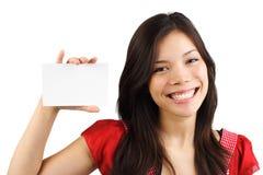 Frau, die unbelegte Karte/weißes Zeichen anhält Stockfotos