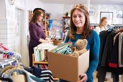 Frau, die unerwünschte Einzelteile zum Nächstenliebe-Shop spendet lizenzfreies stockfoto