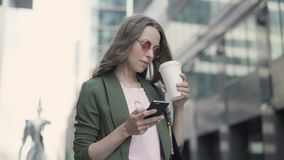 Frau, die in unscharfem surfendem und trinkendem Kaffee des Stadtstraßen-Netzes steht stock footage