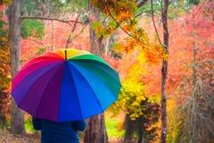 Frau, die unter buntem Regenschirm steht stockfoto