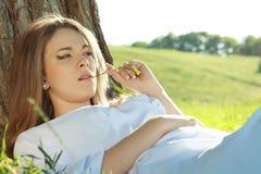 Frau, die unter den Baum legt Stockfotos