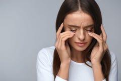 Frau, die unter den Schmerz, glaubender Druck, schmerzliche Augen berührend leidet Lizenzfreies Stockfoto