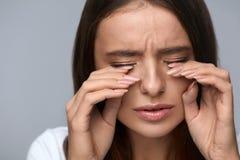 Frau, die unter den Schmerz, glaubender Druck, schmerzliche Augen berührend leidet Stockbilder