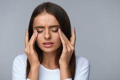 Frau, die unter den Schmerz, glaubender Druck, schmerzliche Augen berührend leidet Stockfotografie
