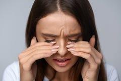 Frau, die unter den Schmerz, glaubender Druck, schmerzliche Augen berührend leidet Stockfotos