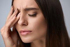 Frau, die unter den starken Schmerz, Kopfschmerzen, rührendes Gesicht habend leidet stockbilder
