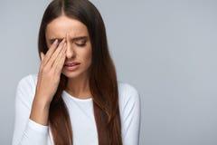 Frau, die unter den starken Schmerz, Kopfschmerzen, rührendes Gesicht habend leidet stockfoto
