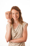 Frau, die unter der glücklichen Maske sich versteckt. Stockfoto