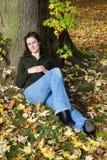Frau, die unter einem Baum sich entspannt Stockfotografie