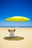 Frau, die unter einem Strandregenschirm stillsteht Stockbilder