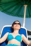 Frau, die unter grünem Sonnenregenschirm ein Sonnenbad nimmt Lizenzfreie Stockfotos