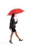 Frau, die unter roten Regenschirm geht Lizenzfreies Stockfoto