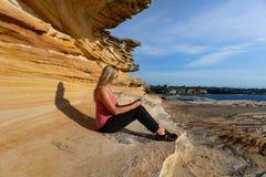 Frau, die unter Sandsteinfelsenleiste durch den Ozean sitzt lizenzfreie stockfotos