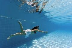 Frau, die unter Wasser in einem Pool schwimmt lizenzfreie stockfotos