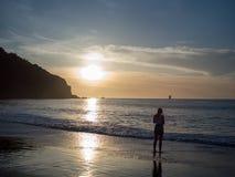 Frau, die untergehende Sonne über dem Pazifischen Ozean beobachtend Stockfotografie