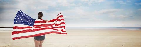 Frau, die USA-Flagge gegen Strandhintergrund hält Stockbilder