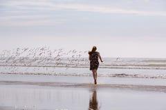 Frau, die Vögel auf Strand jagt stockbild