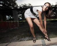 Frau, die verbiegt, um ihren Schuh zu gurten Stockbild