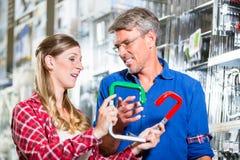 Frau, die Verkäufer im Baumarkt nach Montagen fragt Lizenzfreie Stockbilder
