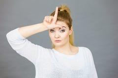 Frau, die Verlierergeste mit L auf Stirn zeigt stockfotos