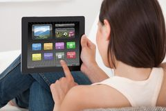 Frau, die verschiedene Anwendungen auf digitaler Tablette verwendet Stockbilder
