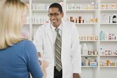 Frau, die verschreibungspflichtige Medikamente an der Apotheke aufhebt Lizenzfreies Stockfoto