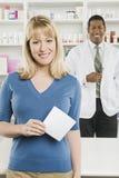 Frau, die verschreibungspflichtige Medikamente an der Apotheke aufhebt Lizenzfreie Stockbilder