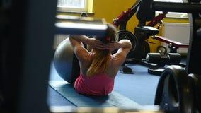 Frau, die versucht, Gewicht zu verlieren Junge Frau in der Sportkleidung, die Eignung tut, trainiert mit Eignungsball an der Turn stock footage
