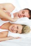 Frau, die versucht, mit dem schnarchenden Mann zu schlafen Lizenzfreie Stockfotos