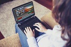 Frau, die Video mit einem Laptop beim zu Hause sitzen redigiert Lizenzfreie Stockfotos
