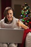 Frau, die Videochat mit Familie vor Weihnachtsbaum hat Stockbild