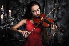 Frau, die Violine im mystischen Innenraum spielt stockfoto