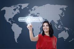 Frau, die virtuellen Startknopf bedrängt Stockbild