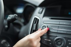 Frau, die Volumen auf Autoradio justiert stockfotos