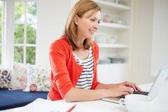 Frau, die vom Haus unter Verwendung des Laptops in der Küche arbeitet Stockfotografie