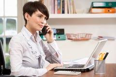 Frau, die vom Haus unter Verwendung des Laptops am Telefon arbeitet Stockfotos