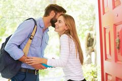 Frau, die vom Mann nach Hause verlässt mit Lunchpaket Abschied nimmt Lizenzfreies Stockbild