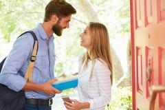 Frau, die vom Mann nach Hause verlässt mit Lunchpaket Abschied nimmt Lizenzfreie Stockbilder