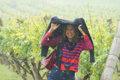 Frau, die vom Regen im Weinberg schützt Stockfotos
