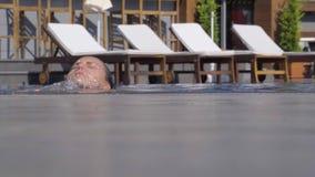 Frau, die vom Wasser im Swimmingpool herauskommt stock video footage