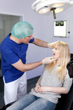 Frau, die von einem Zahnmedizinisch-Chirurgen überprüft wird. Stockfotografie
