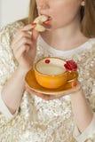 Frau, die von einer schönen handgemachten orange Schale trinkt Stockfoto