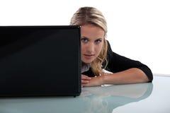 Frau, die von hinten Laptop blickt Stockbild