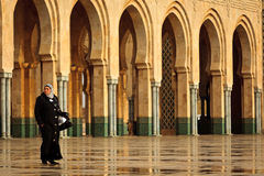Frau, die vor Bögen an der Moschee geht Lizenzfreie Stockbilder