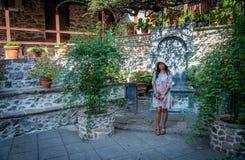 Frau, die vor Brunnen und Steinwand steht und lächelt stockfotografie