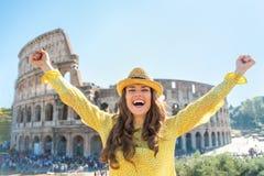 Frau, die vor colosseum in Rom sich freut Stockfoto