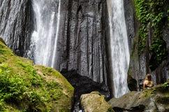 Frau, die vor dusun kuning Wasserfall, Bali meditiert Stockbilder