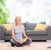 Frau, die vor einem Sofa sitzt und Buch hält Stockfotografie