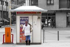 Frau, die vor einer Maschine steht, um Passfotos zu machen Lizenzfreie Stockfotografie