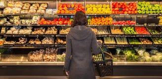 Frau, die vor einer Reihe des Erzeugnisses in einem Gemischtwarenladen steht stockbild